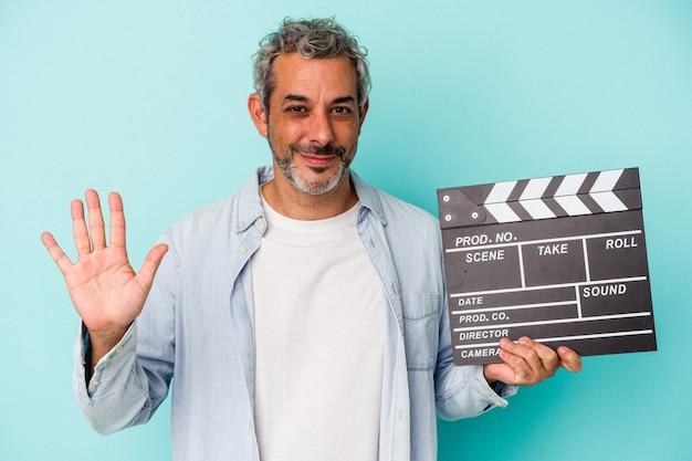 Homme caucasien d'âge moyen tenant un clap isolé sur fond bleu souriant joyeux montrant le numéro cinq avec les doigts.