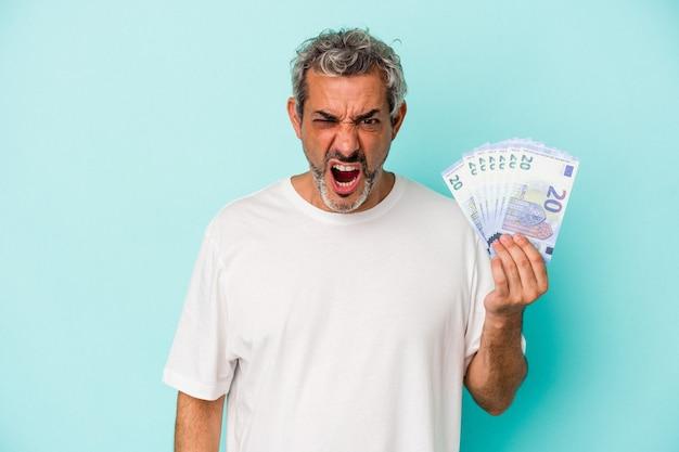 Homme caucasien d'âge moyen tenant des factures isolées sur fond bleu criant très en colère et agressif.