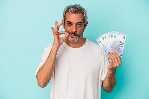 Homme caucasien d'âge moyen tenant des factures isolées sur fond bleu avec les doigts sur les lèvres gardant un secret.