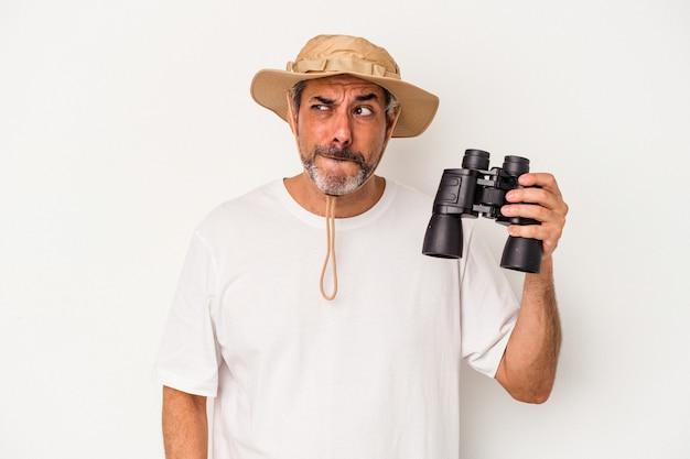Homme caucasien d'âge moyen tenant des jumelles isolées sur fond blanc confus, se sent dubitatif et incertain.