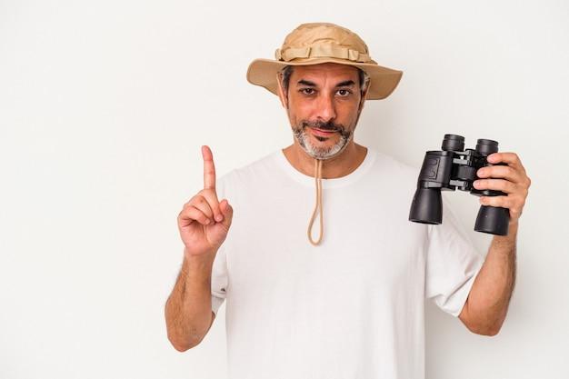 Homme caucasien d'âge moyen tenant des jumelles isolées sur fond blanc montrant le numéro un avec le doigt.