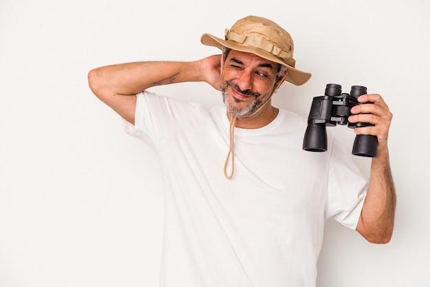 Homme caucasien d'âge moyen tenant des jumelles isolées sur fond blanc touchant l'arrière de la tête, pensant et faisant un choix.
