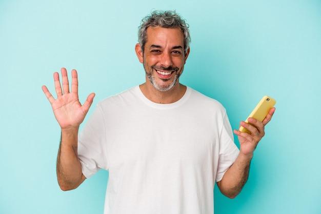 Homme caucasien d'âge moyen tenant un téléphone portable isolé sur fond bleu souriant joyeux montrant le numéro cinq avec les doigts.