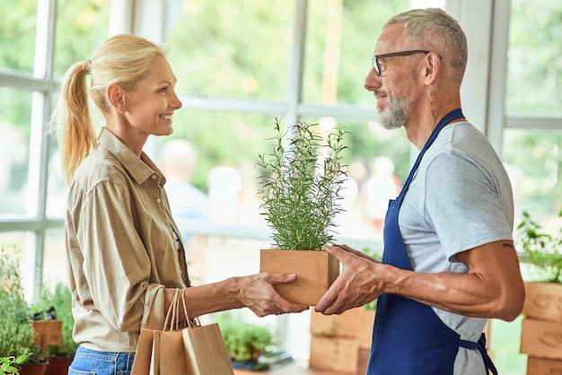 Homme caucasien d'âge moyen vendant du romarin frais à une femme