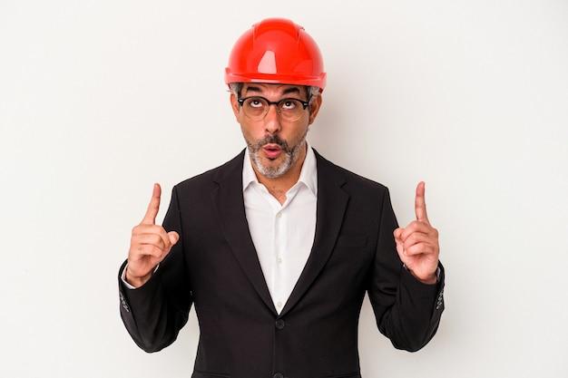 Homme caucasien d'architecte d'âge moyen isolé sur fond blanc pointant vers le haut avec la bouche ouverte.