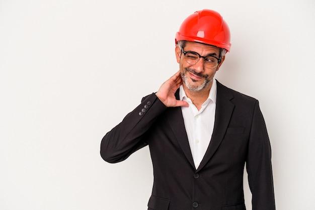 Homme caucasien d'architecte d'âge moyen isolé sur fond blanc touchant l'arrière de la tête, pensant et faisant un choix.