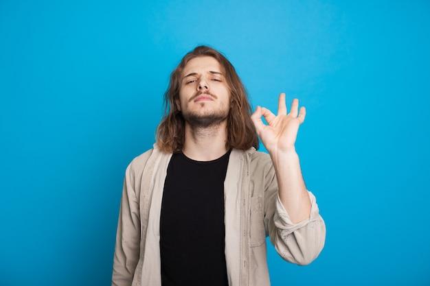 Homme caucasien aux cheveux longs avec barbe fait signe le signe correct tout en posant avec confiance sur un fond bleu