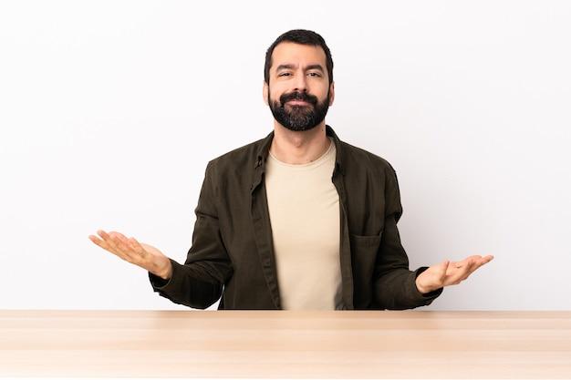 Homme caucasien avec barbe dans une table ayant des doutes