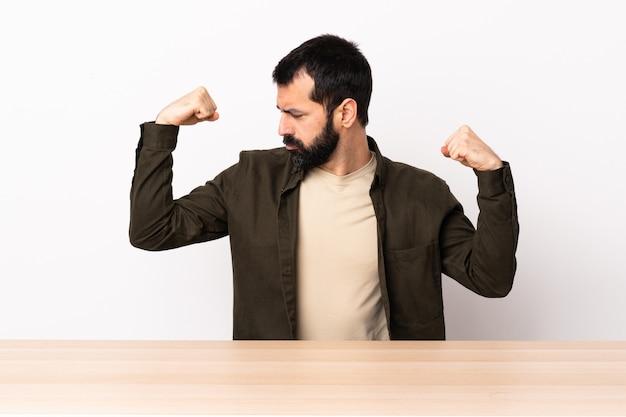 Homme caucasien avec barbe dans une table faisant un geste fort.