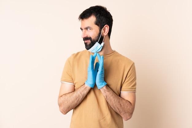 Homme caucasien, à, barbe, protéger, à, a, masque, et, gants, sur, mur, comploter, quelque chose