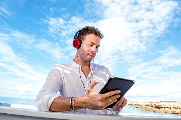Homme caucasien beau et réussi travaillant avec un ordinateur portable sur la plage. travail indépendant et à distance. étudiant sur la rive méditerranéenne