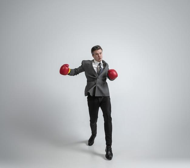 Homme caucasien en boxe de vêtements de bureau avec deux gants rouges sur fond gris.