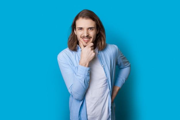 Homme caucasien confiant avec barbe et cheveux longs sourit dans une chemise à la caméra touchant le menton