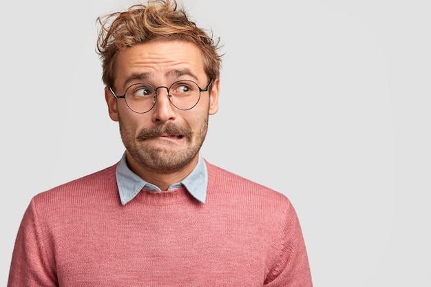 Un homme caucasien confus et désemparé mord la lèvre inférieure et regarde avec une expression anxieuse de côté, s'inquiète avant quelque chose d'important dans la vie, prend une décision, habillé avec désinvolture, isolé sur un mur blanc