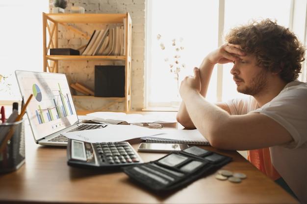 Homme caucasien contrarié et désespéré regardant des rapports financiers et économiques