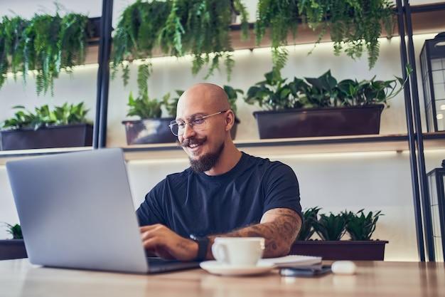 Un homme caucasien du millénaire travaille sur un ordinateur au bureau à domicile tient un stylo dans sa main un travail à distance