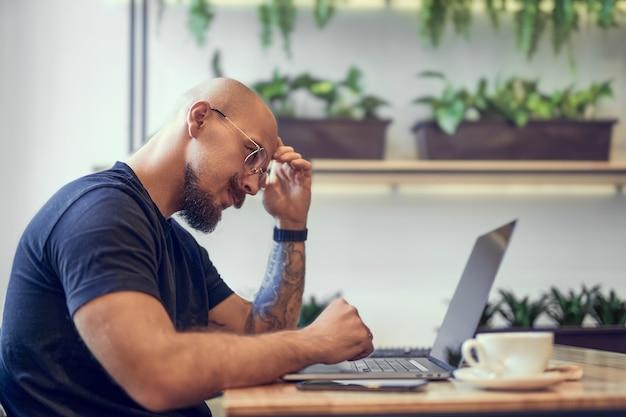 Un homme caucasien du millénaire travaille sur un ordinateur au travail à distance au bureau à domicile