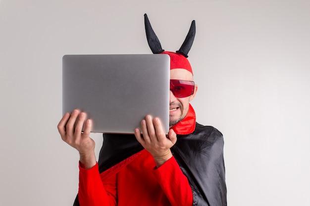 Homme caucasien élégant au chapeau de diable avec des cornes et cape de vampire avec ordinateur portable