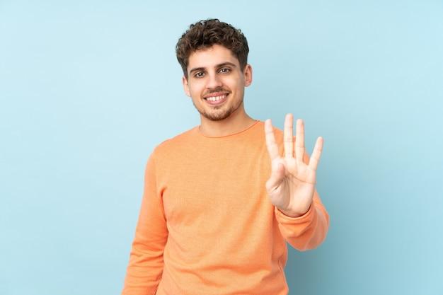 Homme caucasien isolé sur bleu heureux et comptant quatre avec les doigts