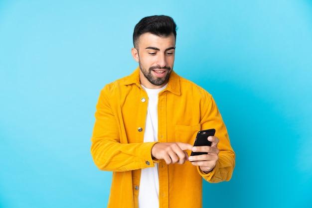 Homme caucasien isolé envoyant un message ou un e-mail avec le mobile