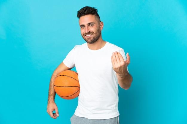 Homme caucasien isolé sur fond bleu jouant au basket et faisant le geste à venir