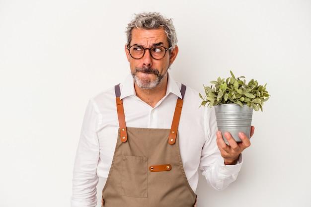 Homme caucasien de jardinier d'âge moyen tenant une plante isolée sur fond blanc confus, se sent dubitatif et incertain.