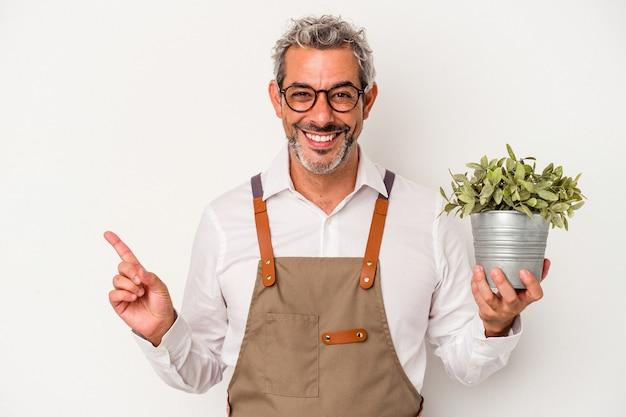 Homme caucasien de jardinier d'âge moyen tenant une plante isolée sur fond blanc souriant et pointant de côté, montrant quelque chose dans un espace vide.