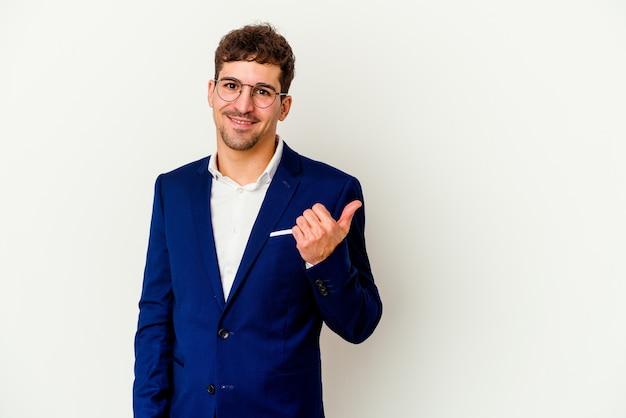 Homme caucasien jeune entreprise isolé sur fond blanc choqué de pointer avec l'index vers un espace de copie.