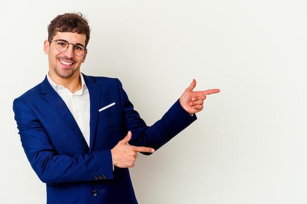 Homme caucasien jeune entreprise isolé sur fond blanc souriant joyeusement pointant avec l'index loin.