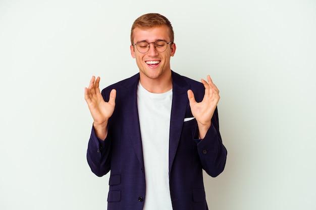 Homme caucasien jeune entreprise isolé sur mur blanc joyeux rire beaucoup. concept de bonheur.