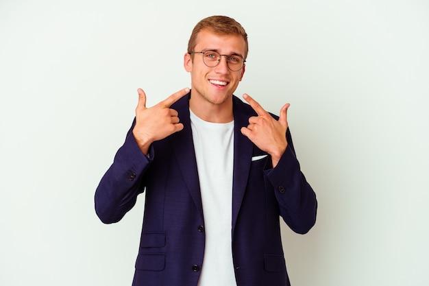 Homme caucasien jeune entreprise isolé sur des sourires blancs, pointant du doigt la bouche.