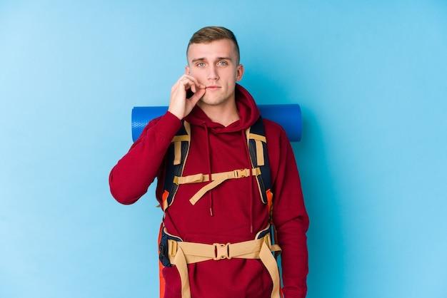 Homme caucasien jeune voyageur avec les doigts sur les lèvres en gardant un secret.