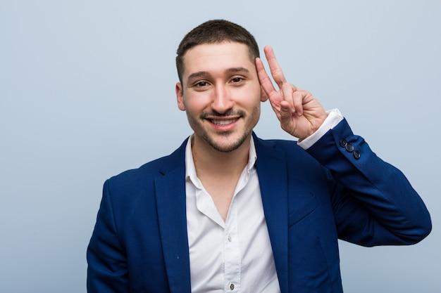 Homme caucasien de jeunes entrepreneurs montrant le signe de la victoire et souriant largement.