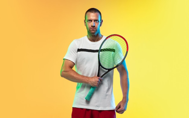 Un homme caucasien jouant au tennis isolé sur studio