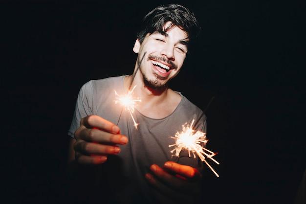 Homme caucasien jouant avec des feux de bengale