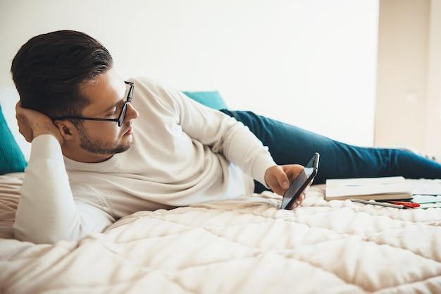 Homme caucasien avec des lunettes couché dans son lit et bavarder au téléphone après avoir suivi des cours en ligne