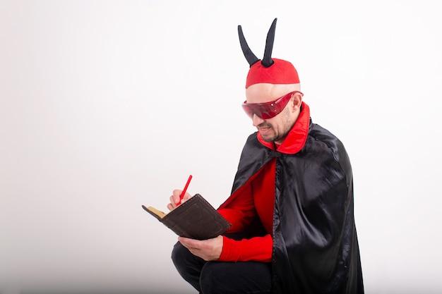 Homme caucasien en lunettes de soleil rouges et costume d'halloween avec stylo et cahier sur fond de studio blanc.