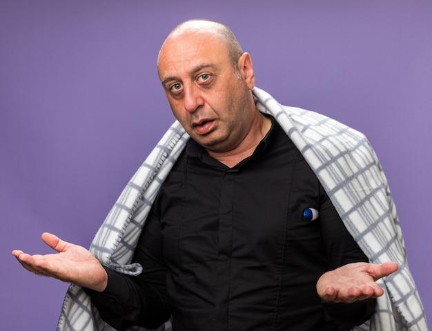 Homme caucasien malade adulte désemparé enveloppé dans un plaid mesurant la température avec un thermomètre et gardant les mains ouvertes isolées sur un mur violet avec espace de copie