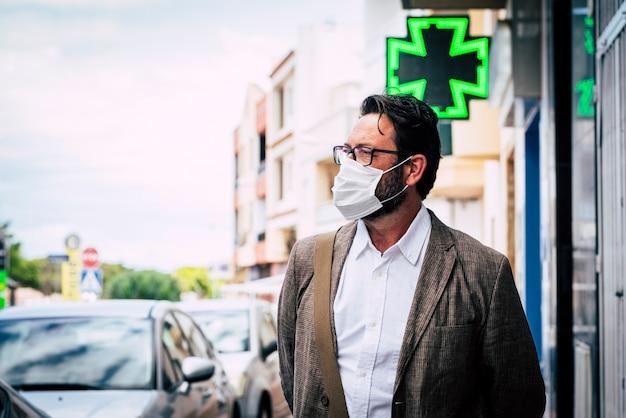 Homme caucasien mature adulte marche en plein air dans la ville à l'aide d'un masque