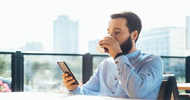 Homme caucasien occupé avec barbe à discuter au téléphone tout en buvant une tasse de café à la cafétéria