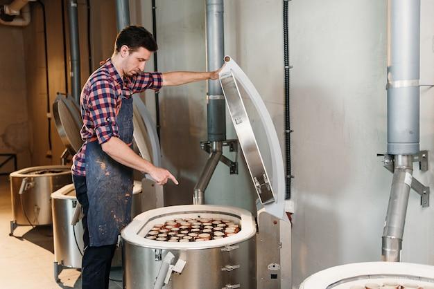 Homme caucasien ouvrant le four pour la cuisson des pots en céramique.