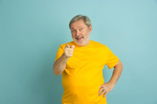Homme caucasien pointant, vous choisissant isolé sur bleu