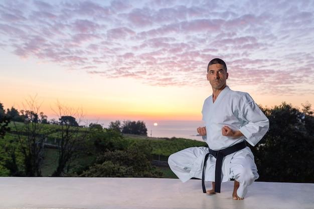 Homme caucasien pratiquant le karaté dans la nature avec un coucher de soleil sur la mer