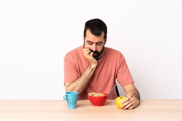 Homme caucasien prenant son petit déjeuner dans une table ayant des doutes.