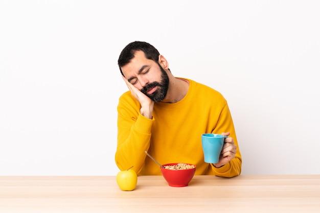 Homme caucasien prenant son petit déjeuner dans une table faisant le geste de sommeil dans une expression dorable.