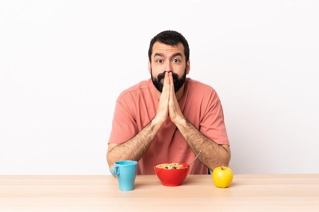 Homme caucasien prenant son petit déjeuner dans une table maintient la paume ensemble. la personne demande quelque chose.