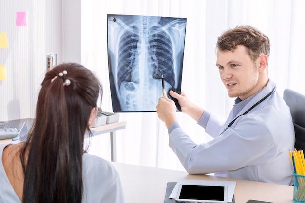 Homme caucasien de professionnels de la santé tenant aux rayons x et conversant avec le patient.