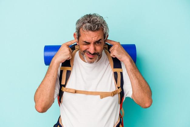 Homme caucasien de randonneur d'âge moyen isolé sur fond bleu couvrant les oreilles avec les mains.