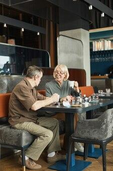 Homme caucasien senior positif assis à table et buvant du thé tout en parlant à un ami au café pendant le rassemblement