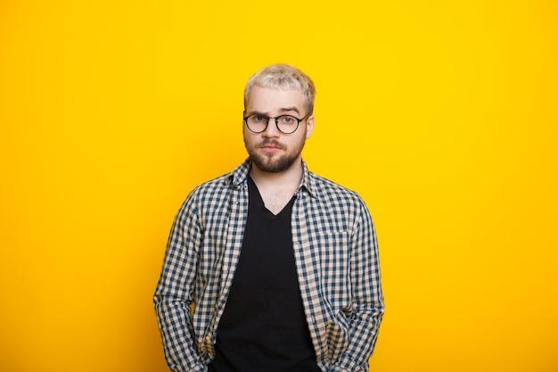 Homme caucasien sérieux aux cheveux blonds à travers des lunettes et faisant des gestes avec son sourcil sur un mur jaune